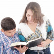Stock Photo: Mother and son reading a Bible over a black background