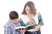 Mother and son reading a Bible over a black background — Stock Photo
