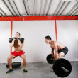 Foto Stock: Group of two exercising using barbells in gym and kettleb