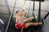 Crossfit rope climb exercise. Focus in the body. — Photo