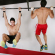 Stock Photo: Athletic group executing exercise tightening on horizontal bar.