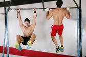 Athletic group executing exercise tightening on horizontal bar. — Stock Photo