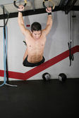Ring dip crossfit exercise over a dark background. — Stock Photo