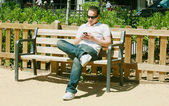 Young man text messaging in park — Stock Photo