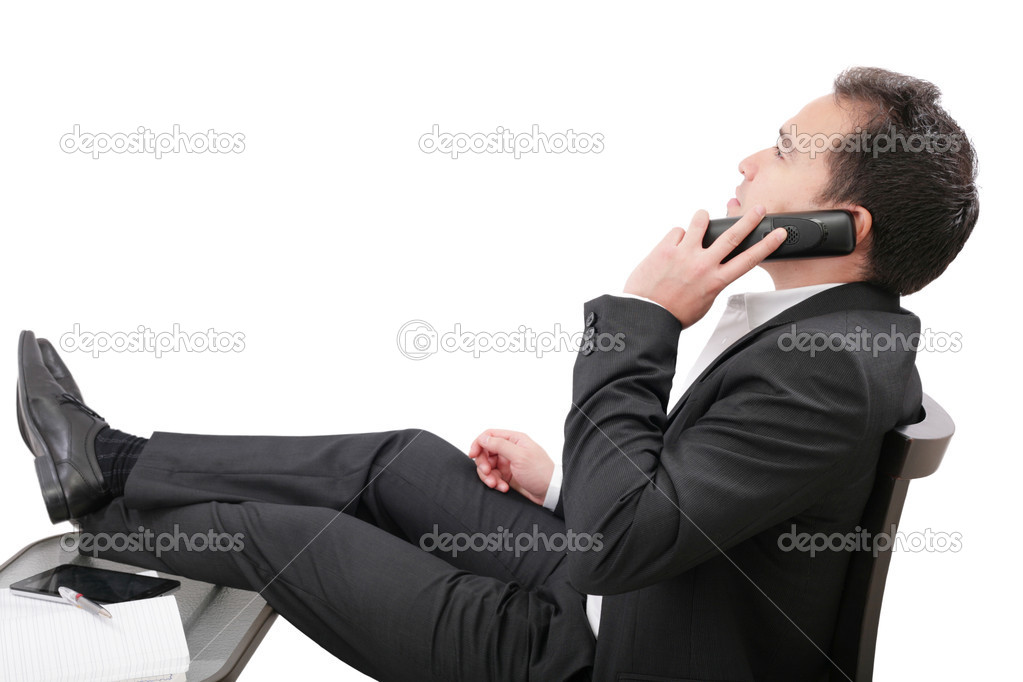Young business man relaxing at office desk and talking on mobile phone, isolated on white  — Stock Photo #19534565