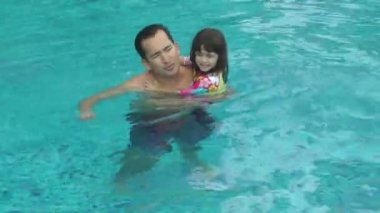 Daughter kisses her father in the pool. They are happy. — Stock Video