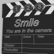 Movie production clapper board notifying to the that smil — Stok fotoğraf