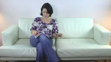 Concentrated woman reading a magazine sitting on sofa — Stock Video