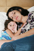 Beautiful young mother and her daughter on the bed — Stock Photo