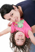 Mother playing with her daughter and holding her upside down — Stock Photo