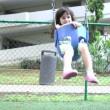 Slow motion, a little girl swings on a swing set — Stock Video #26905389