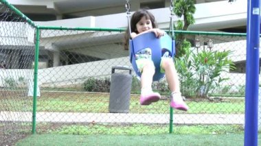 Slow motion, a little girl swings on a swing set — Stock Video
