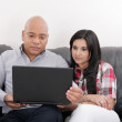 Young couple thinking and looking at a laptop computer — Stock Photo