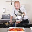 Stock Photo: Chef in kitchen cooking, he is working on sauce for food