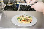 Cibo italiano. chef mettendo il parmigiano sopra un rigatoni con vegetab — Foto Stock