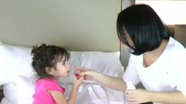 Little girl in bed taking medicine — Stock Video