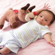 Hispanic baby with teddy bear laying on bed — Stock Photo