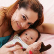 Happy mum and baby boy smiling in the bed holding teddy bear — Stock Photo #30831423
