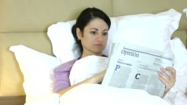 Woman reading newspaper lying on bed at home — Vídeo de stock