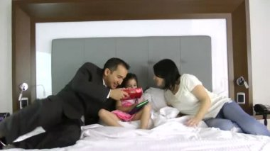 Father and mother giving a gift to his little daughter in the bedroom — 图库视频影像