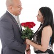 Happy couple holding a bouquet of red roses isolated — Stock Photo