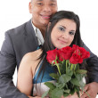 Portrait of happy couple with flowers, looking at camera. — Stock Photo
