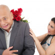 Woman striking his boysfriend with a bouquet of red roses. Focu — Stock Photo #39589933