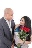 Young couple with bouquet of roses looking at each other — Stock Photo