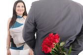 Man with a bouquet of red roses watching his woman isolated, val — Stock Photo