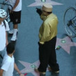 Stock Video: HOLLYWOOD, Californi- CIRC2014: tourists gather around street performer in Hollywood at sunset on CIRC2014 in Hollywood.