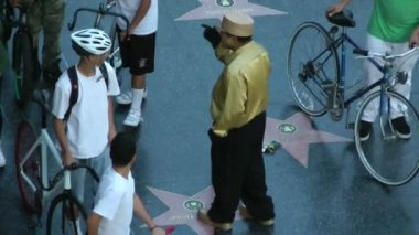 HOLLYWOOD, California - CIRCA 2014: tourists gather around a street performer in Hollywood at sunset on CIRCA 2014 in Hollywood. — Stock Video