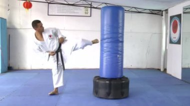Black belt Karate Man practicing in the sandbag — Stock Video
