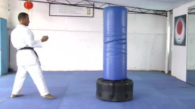 Black belt karate practicing kicking the sandbag — Stock Video