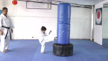 Little girl practicing kicks with the sandbag — Stock Video