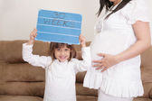 Girl holding a 30 weeks sign to her expectant mother — Stock Photo