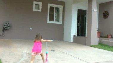 Niña dejando caer su scooter frente a ella la casa y entrar — Vídeo de stock