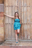 Beautiful woman in the dress in old wooden door — Stock Photo