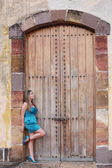 Young woman in long dress standing in front an old door.  Focus  — Stock Photo