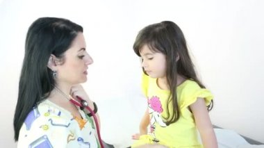Doctor teaching the use of the stethoscope to a girl — Stock Video