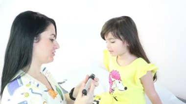 Female Pediatrician performing an eye exam on a female child — Stock Video