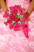 A red bridal bouquet in the hands of the bride dresses pink — Stock Photo
