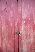 Wooden door with red faded paint — Stock Photo