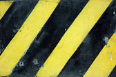 Stare czarne i żółte paski na ścianie — Zdjęcie stockowe