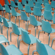 Arrangement of rows of small blue chairs — Stock Photo #13255408