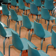 Arrangement of rows of small blue chairs — Stock Photo