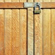 Wooden door locked with a golden padlock - Stock Photo