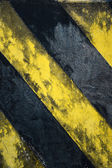 Old black and yellow strips on the wall — Stock Photo
