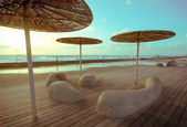 Wooden deck with stone benches and metal with straw umbrellas — Stock Photo