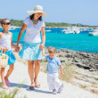 Family of three walking along tropical beach — Stock Photo #13121887