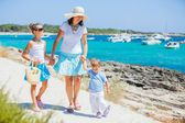 Family of three walking along tropical beach — Stock Photo